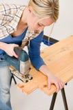 Home improvement - handywoman cutting wooden floor. With jigsaw Stock Photos