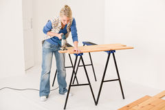 Home improvement - handywoman cutting wooden floor Stock Images