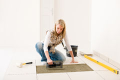 Home improvement - handywoman laying tile. Home improvement, renovation - handywoman laying tile, trowel with mortar stock images