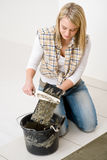 Home improvement - handywoman laying tile. Home improvement, renovation - handywoman laying tile, trowel with mortar royalty free stock photo