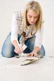 Home improvement - handywoman measuring tile Royalty Free Stock Photo