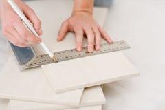 Home improvement - handywoman measuring tile. Focus on ruler Royalty Free Stock Photo