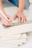 Home improvement - handywoman measuring tile Stock Photos