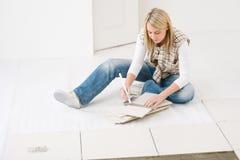 Home improvement - handywoman measuring tile. Home improvement, renovation - handywoman measuring tile Stock Images