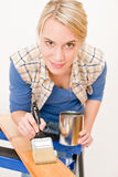 Home improvement - handywoman painting wood. En plank in workshop Royalty Free Stock Photography