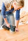 Home improvement - handywoman sanding wooden floor. In workshop Royalty Free Stock Photo
