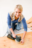 Home improvement - handywoman sanding wooden floor Royalty Free Stock Images