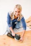 Home improvement - handywoman sanding wooden floor. In workshop Royalty Free Stock Images