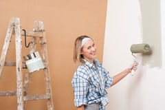 Home improvement: Happy woman painting wall. With paint roller Royalty Free Stock Photos