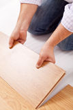 Home improvement - installing laminate flooring. Fitting a plank Stock Photos