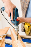 Home improvement - man drilling wood. Home improvement - handyman drilling wood in workshop Royalty Free Stock Image