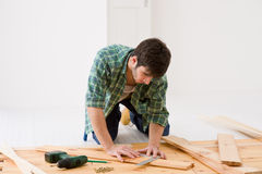 Home improvement - man installing wooden floor Royalty Free Stock Photography