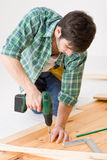 Home improvement - man installing wooden floor Royalty Free Stock Image