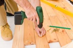 Home improvement - man installing wooden floor. Home improvement - handyman installing wooden floor home Stock Photo