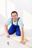 Home improvement - man laying isolating foam layer. Worker laying isolating foam layer beneath flooring - measuring and cutting stock photos
