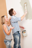 Home improvement Man painting wall with paintbrush. Home improvement: Man painting wall with paintbrush holding paint can royalty free stock image