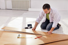 Home improvement - redecorating. Home improvemant - man laying new laminate flooring in empty room stock image