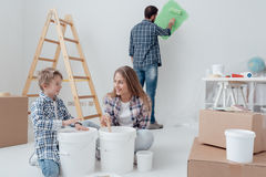 Home improvement and renewal. Young family doing a home makeover and painting rooms, the father is painting walls with a paint roller, the mother and her son are Stock Image