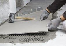 Home improvement, renovation - construction worker tiler is tili Stock Photo