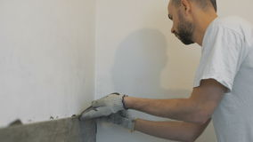 Home improvement, renovation - construction worker tiler is tiling, ceramic tile wall adhesive, trowel with mortar stock footage
