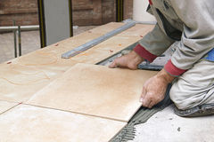 Home improvement, renovation - construction worker tiler is tiling. Close up Royalty Free Stock Images