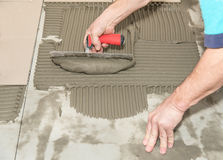 Home improvement, renovation. Construction worker is tiling, ceramic tile. Royalty Free Stock Photos