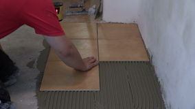 Home improvement, renovation - handyman lay tile on room floor stock footage