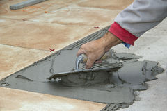 Home improvement, renovation - handyman laying tile with level Stock Photo