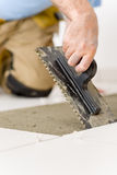 Home improvement, renovation - man laying tile. Home improvement, renovation - handyman laying tile, trowel with mortar royalty free stock images