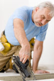 Home improvement, renovation - man laying tile. Home improvement, renovation - handyman laying tile, trowel with mortar stock photo