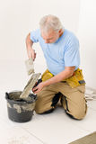 Home improvement, renovation - man laying tile. Home improvement, renovation - handyman laying tile, trowel with mortar stock images