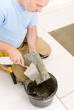 Home improvement, renovation - man laying tile. Home improvement, renovation - handyman laying tile, trowel with mortar stock image