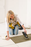 Home improvement, renovation - woman laying tile. Home improvement, renovation - handywoman laying tile, trowel with mortar royalty free stock photo