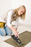 Home improvement, renovation - woman laying tile. Home improvement, renovation - handywoman laying tile, trowel with mortar stock images