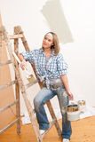 Home improvement: Smiling woman with paint. And brush painting wall royalty free stock photo