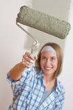 Home improvement: Smiling woman with paint roller Stock Photo