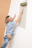 Home improvement: Smiling woman with paint roller Stock Photography