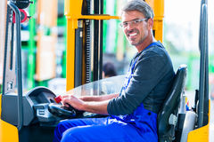 Home improvement store clerk driving forklift Royalty Free Stock Photos