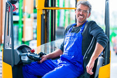 Home improvement store clerk driving forklift. In warehouse for DIY equipment Stock Photography