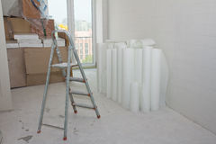 Home improvement. White glass wallpaper rolls and stepladder Stock Photo