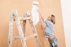 Home improvement: Woman painting wall. With paint roller Royalty Free Stock Photo