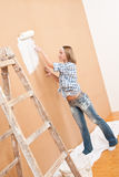 Home improvement: Woman painting wall. With paint roller Stock Images