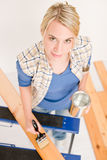 Home improvement - woman painting wooden plank. Home improvement - handywoman painting wooden plank in workshop Stock Image