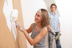 Home improvement: Young couple. Painting wall with paint roller Royalty Free Stock Images