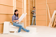 Home improvement young couple with blueprints. Home improvement happy young couple with architectural blueprints building wall Stock Photo