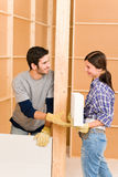 Home improvement young couple building brick wall. Home improvement smiling young couple building new brick panel wall Royalty Free Stock Images