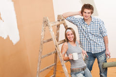 Home improvement: Young couple painting wall Stock Photography