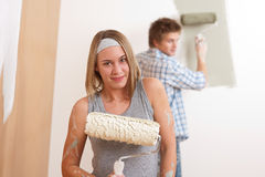 Home improvement: Young couple painting wall Stock Photos