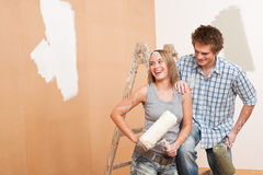 Home improvement: Young couple painting wall. With paint roller Royalty Free Stock Image