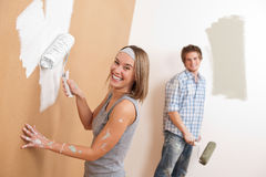 Home improvement: Young couple painting wall. With paint roller Stock Images